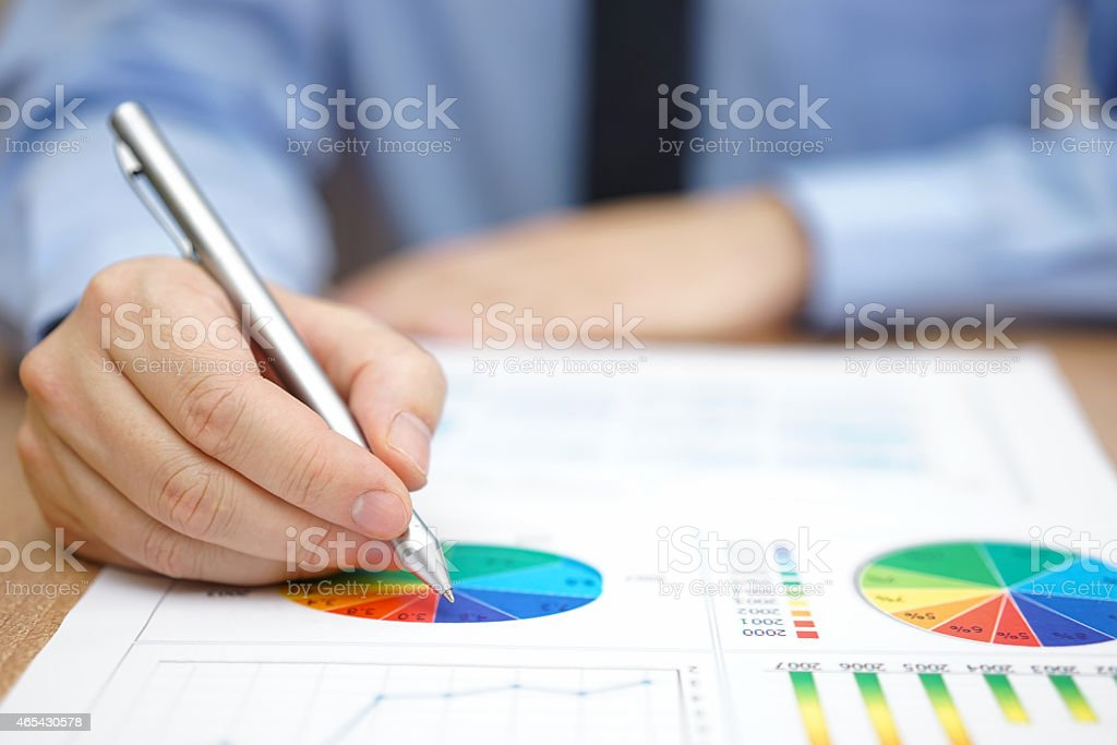 Businessman is analyzing business report with charts and diagrams stock photo
