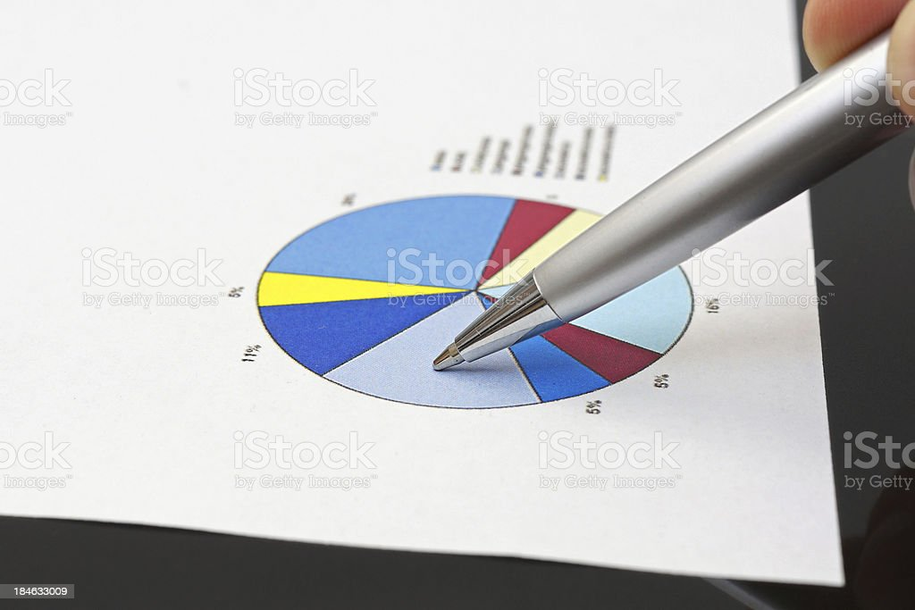 businessman is analyzing financial report on pie chart royalty-free stock photo