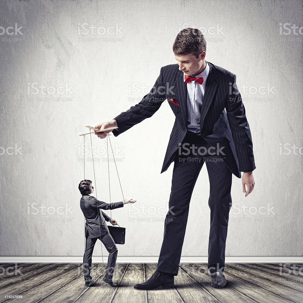 Businessman is being a puppeteer stock photo