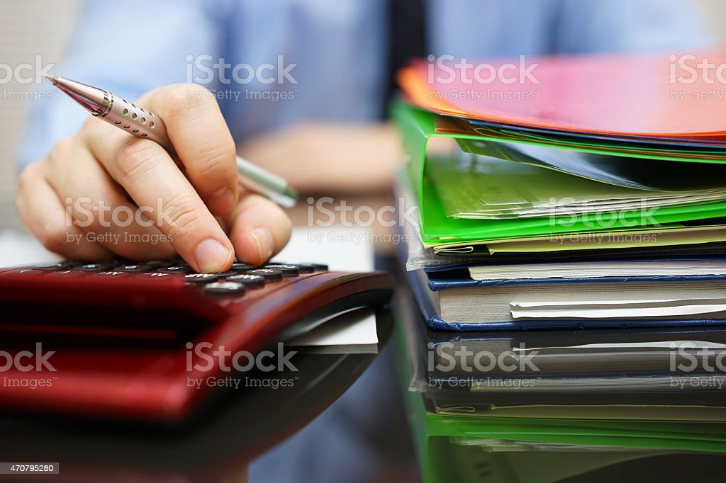 Businessman is calculating and working, with a lot of documentation stock photo