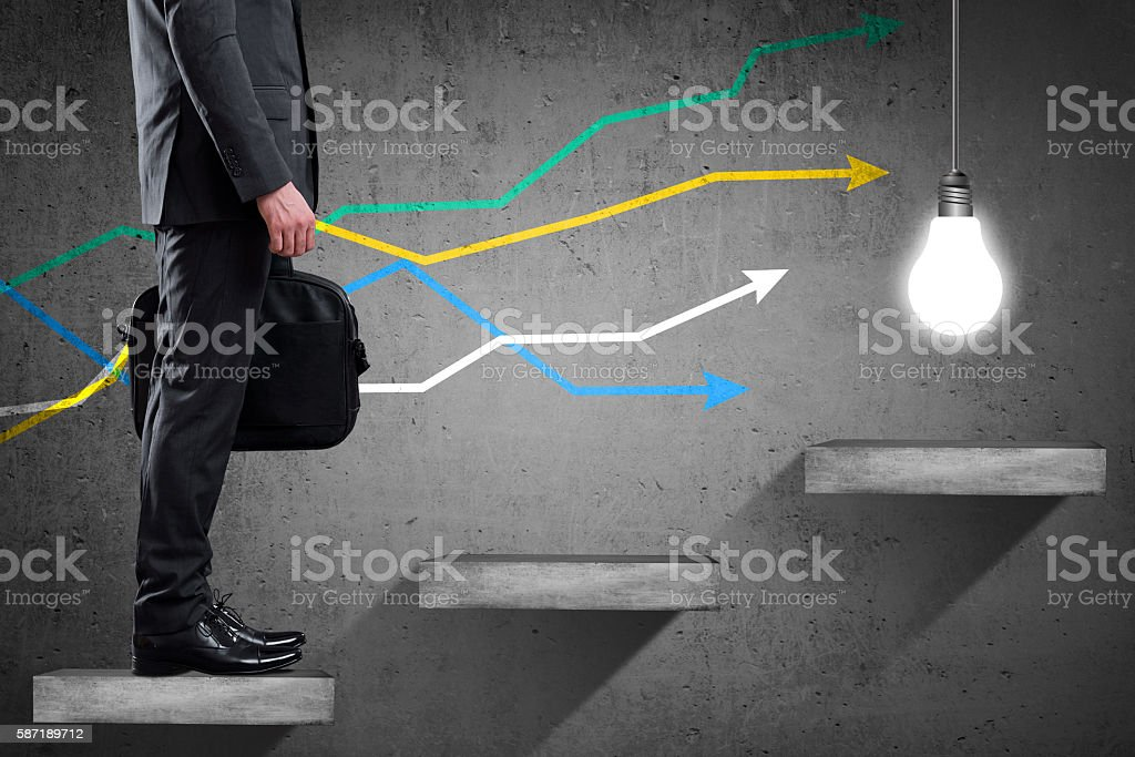 Businessman is climbing up to get Big Idea stock photo