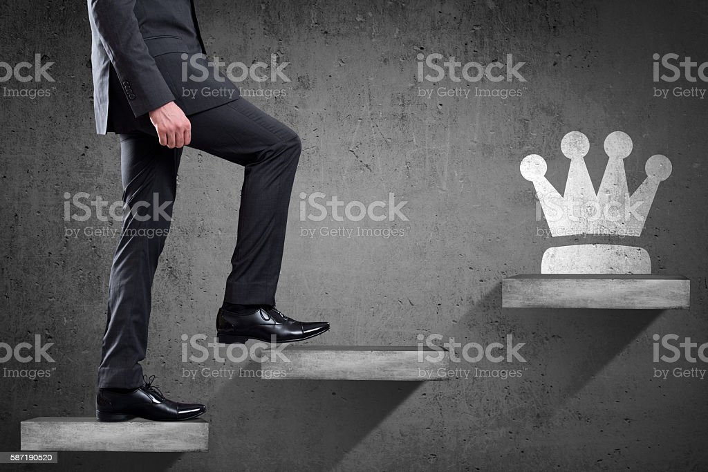 Businessman is climbing up to get crown stock photo