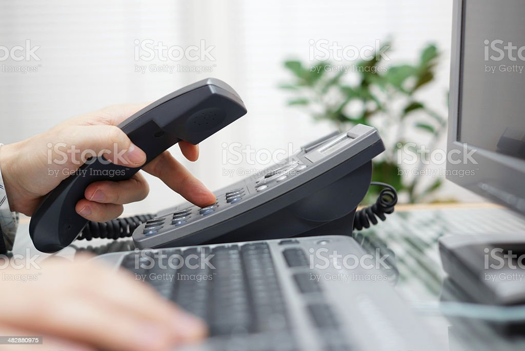 businessman is dialing a phone number in office stock photo