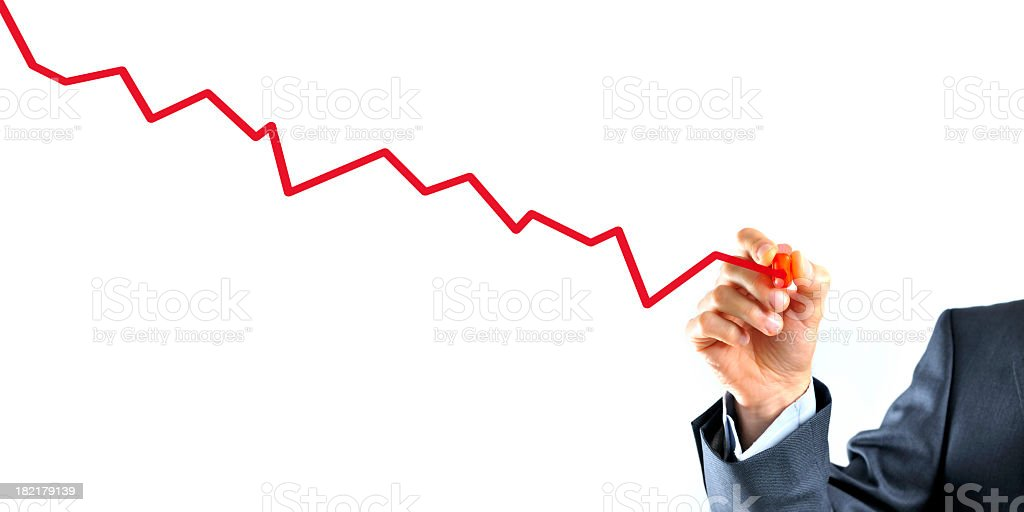 Businessman is drawing a graph with red line going down stock photo