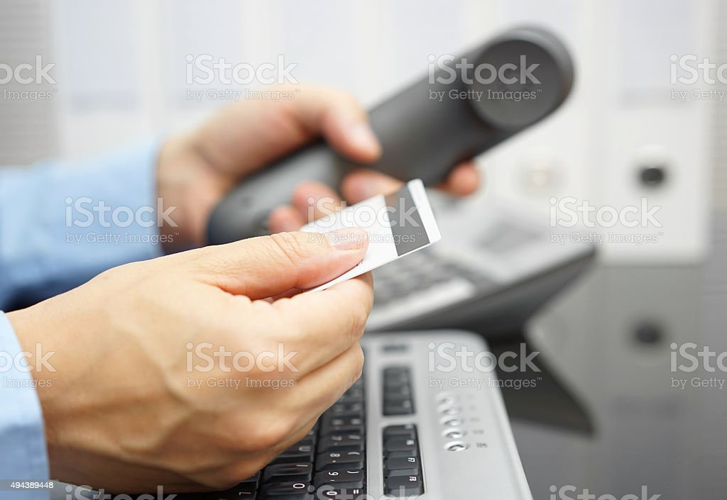businessman is holding credit card and calling bank stock photo