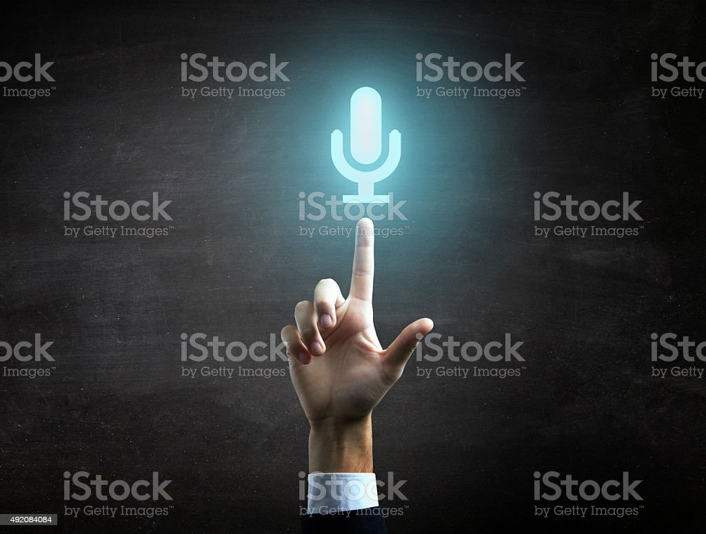 Businessman is indicating  a blue microphone icon on black blackboard stock photo