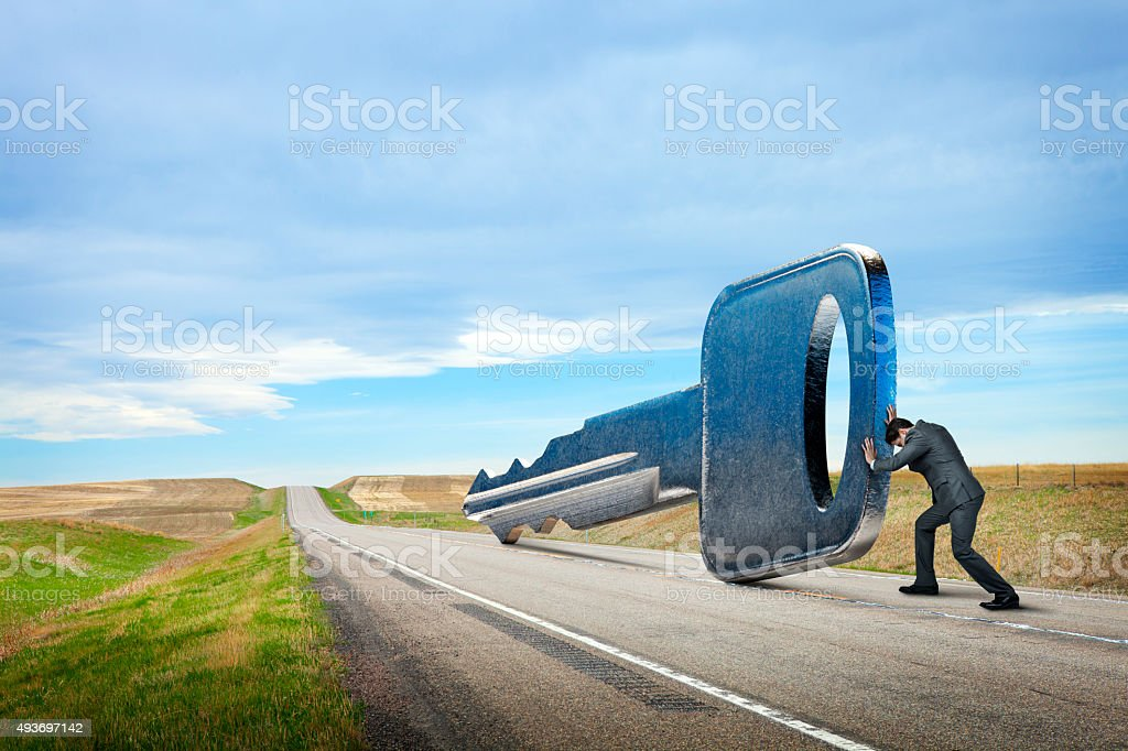 Businessman Is Pushing Key Down A Rural Road stock photo