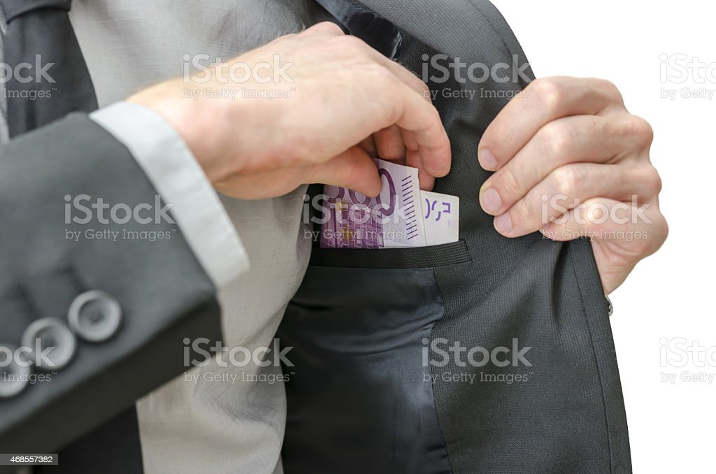 Businessman is putting euros banknotes money in pocke stock photo