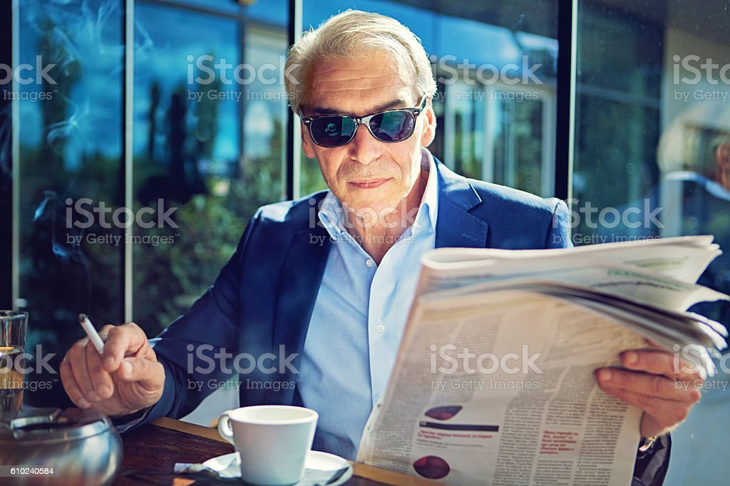 Businessman is reading newspaper stock photo