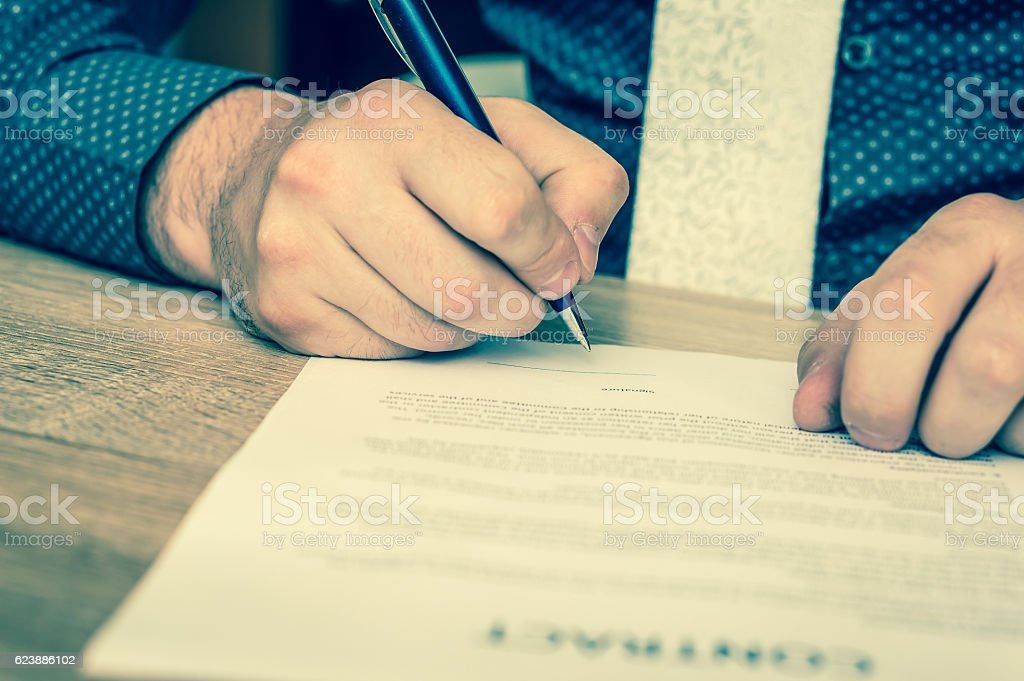 Businessman is signing a contract to conclude a deal stock photo