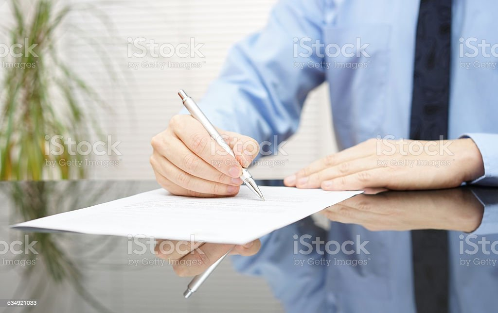 businessman is signing contract to finalize deal stock photo