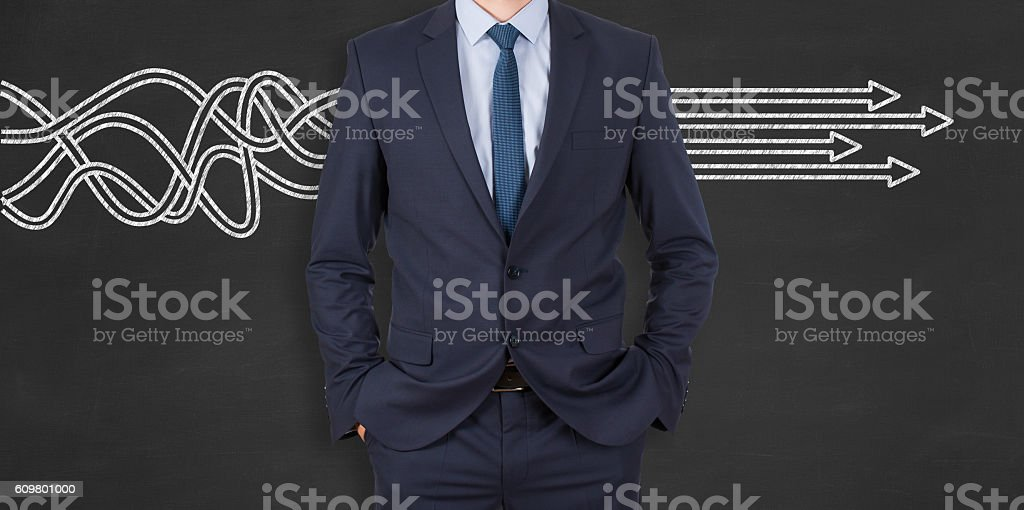 Businessman is standing in front of blackboard with drawn arrows stock photo