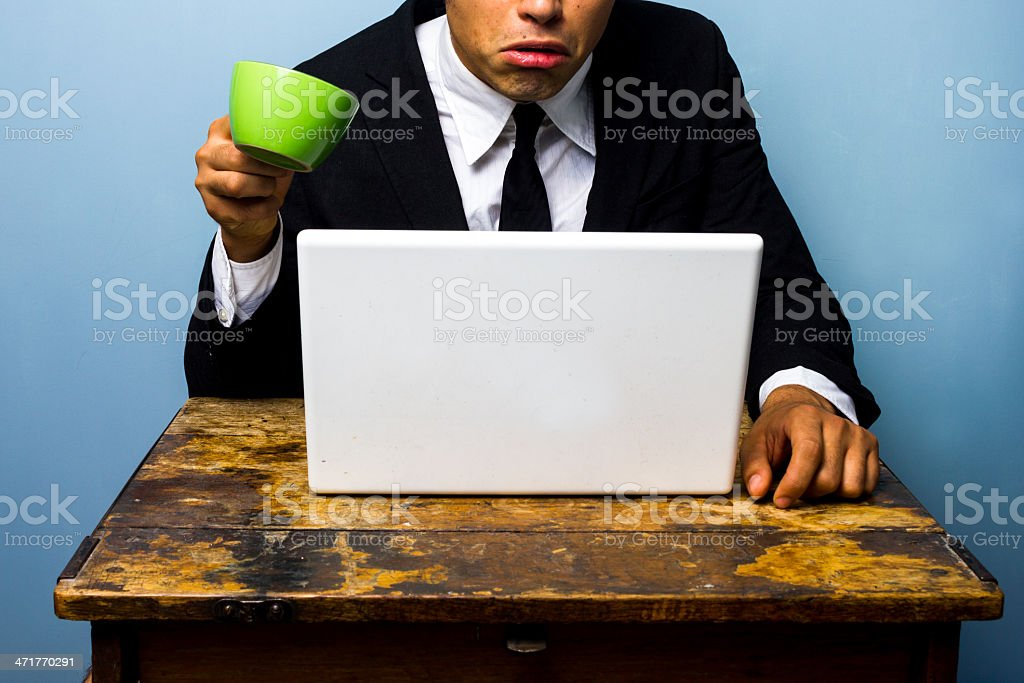 Businessman is surprised and nearly spills coffee on notebook royalty-free stock photo