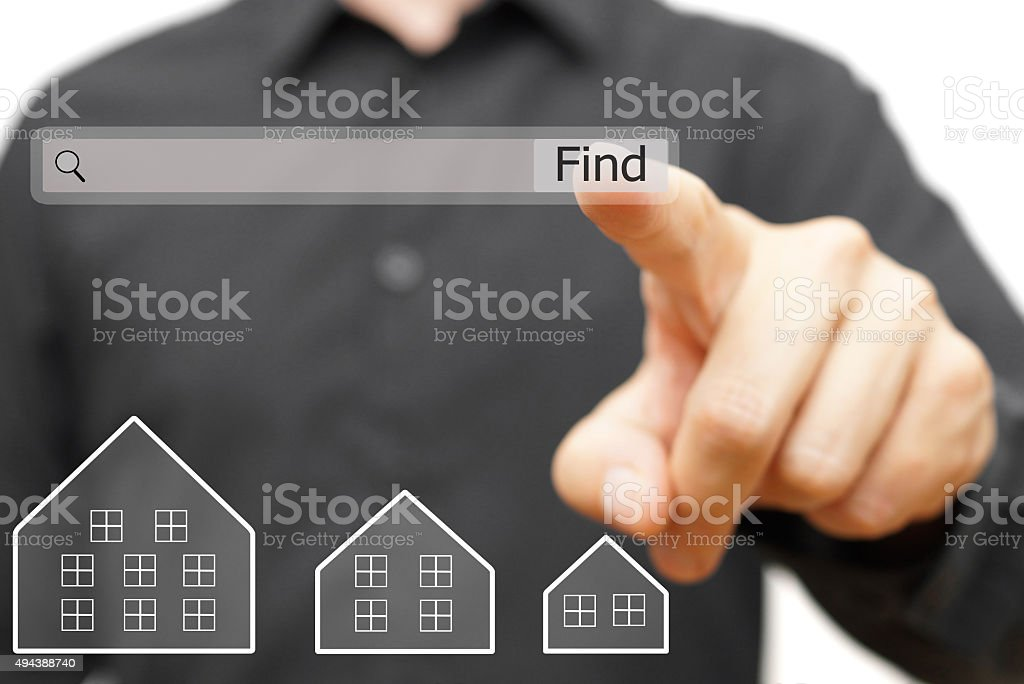 businessman is using internet search bar to  find real estate stock photo