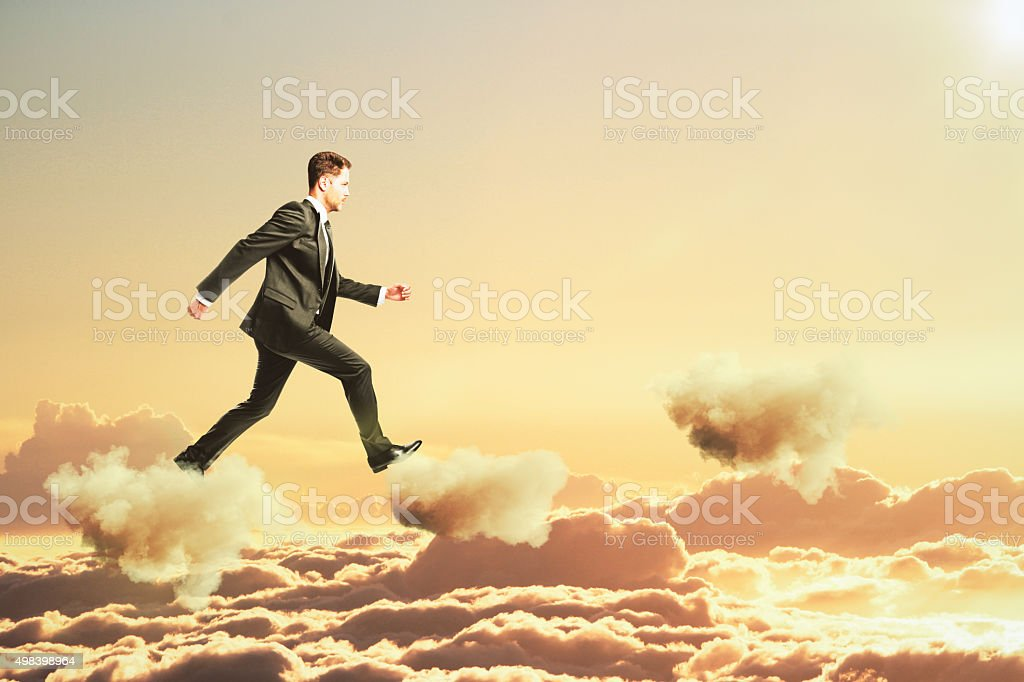 Businessman is walking on clouds in the sky concept stock photo