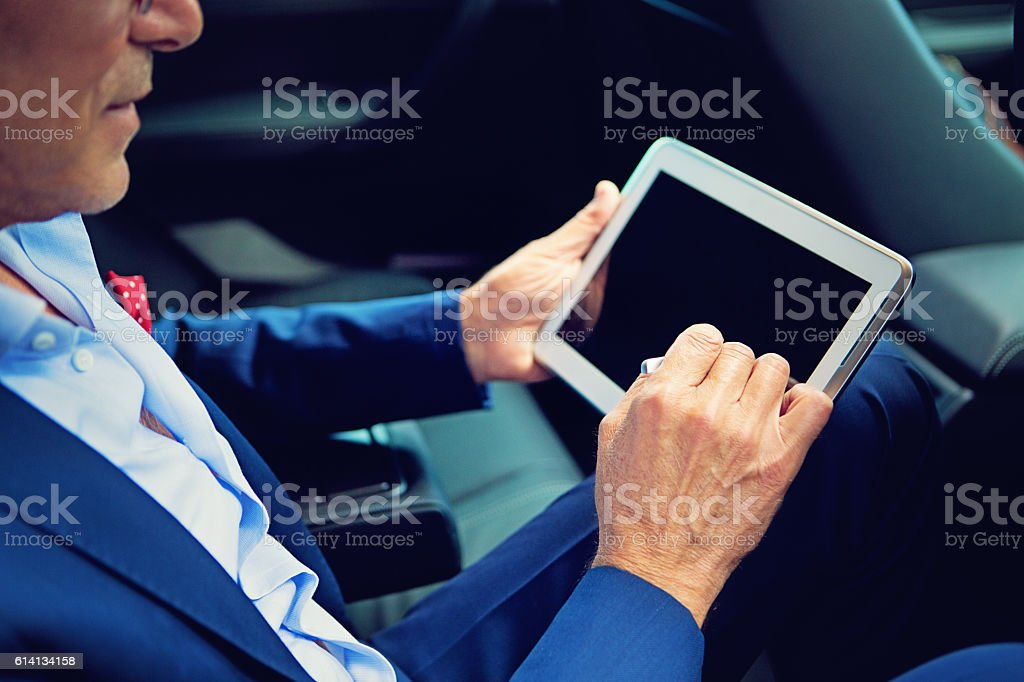 Businessman is working using his tablet in the car stock photo
