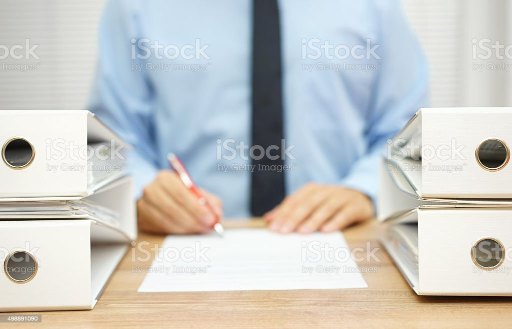 businessman is writing report about .irregularities in company data stock photo
