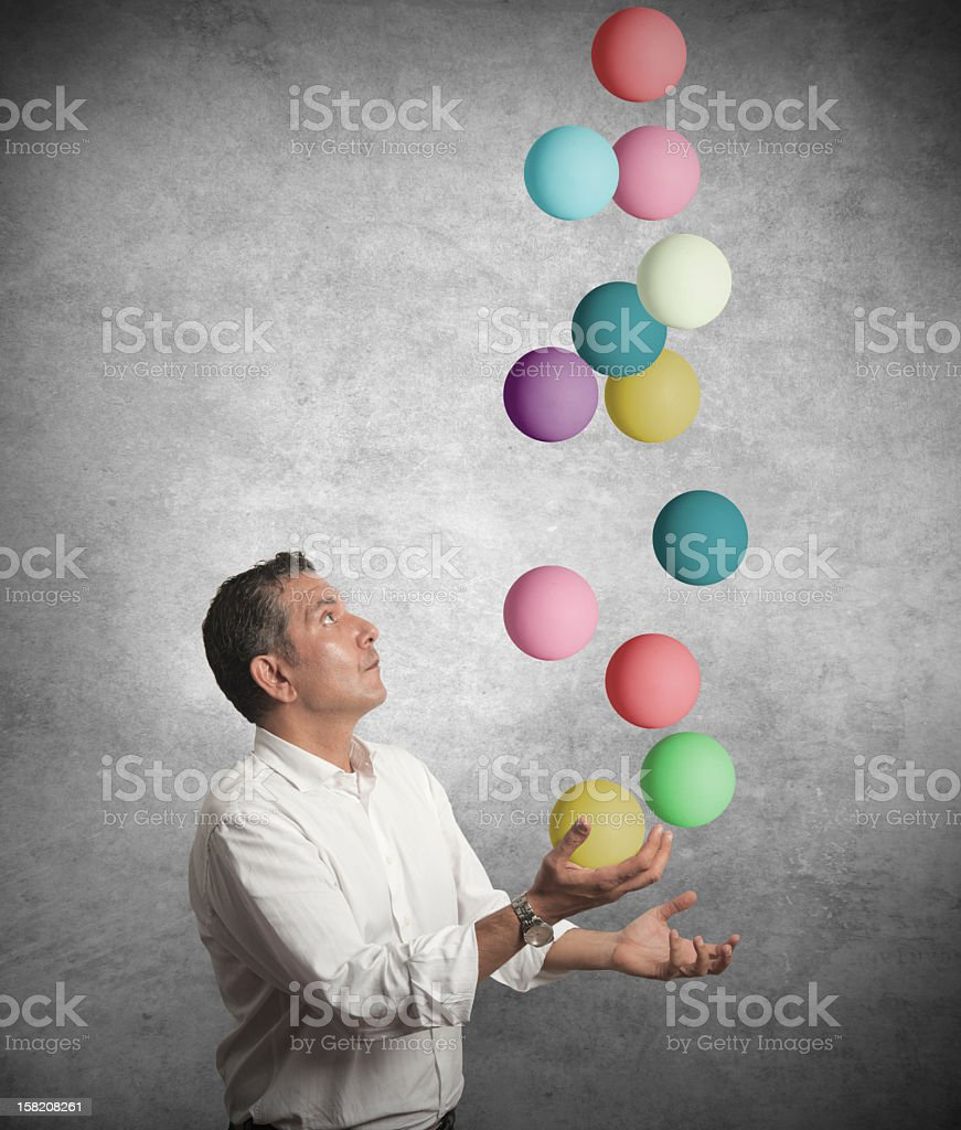 Businessman juggling balls signifying business difficulty stock photo