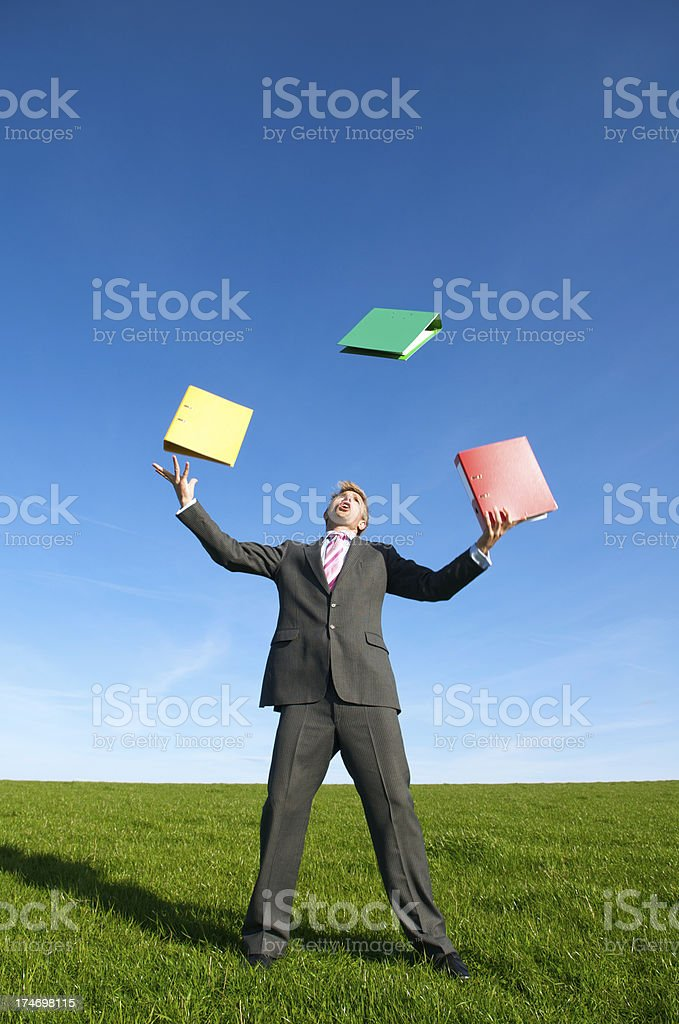 Businessman Juggling File Folders in Bright Meadow royalty-free stock photo
