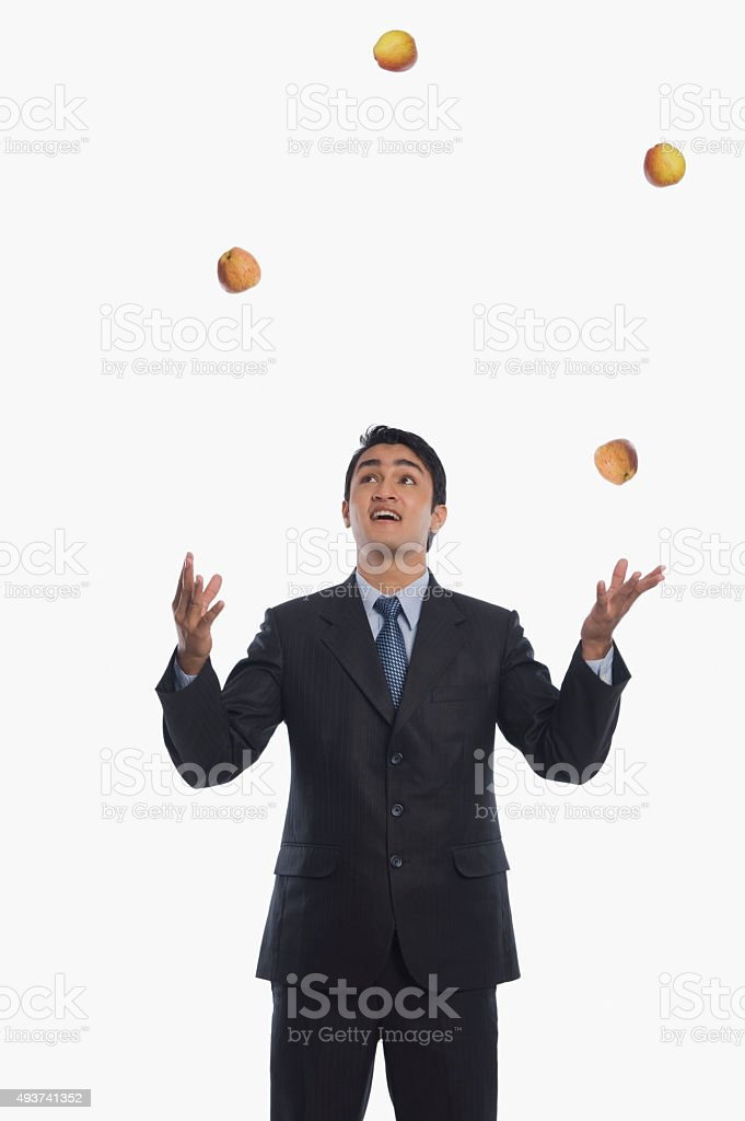 Businessman juggling with apples stock photo