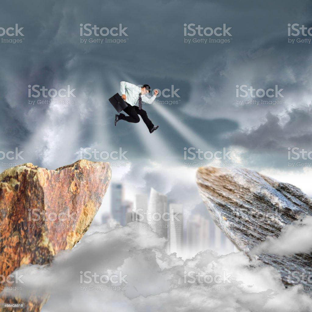Businessman jump over precipice mountain rock stock photo