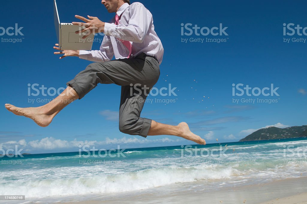 Businessman Jumping Barefoot with Laptop on Tropical Beach royalty-free stock photo
