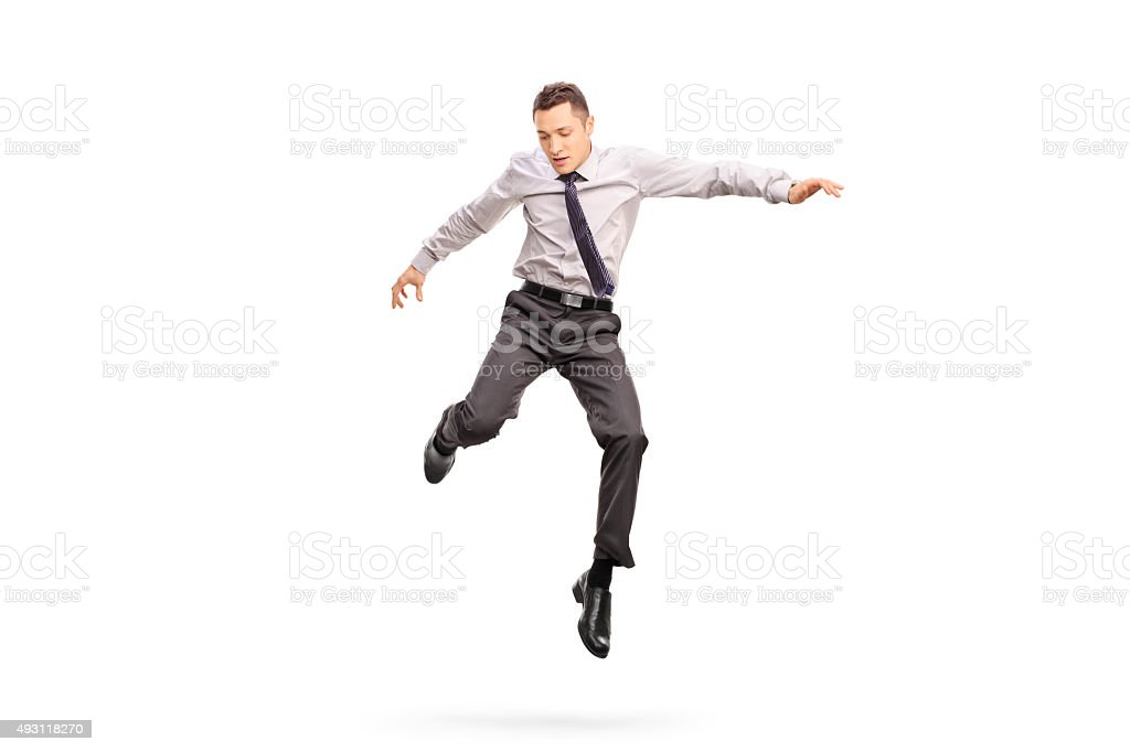 Businessman jumping in the air and looking down stock photo