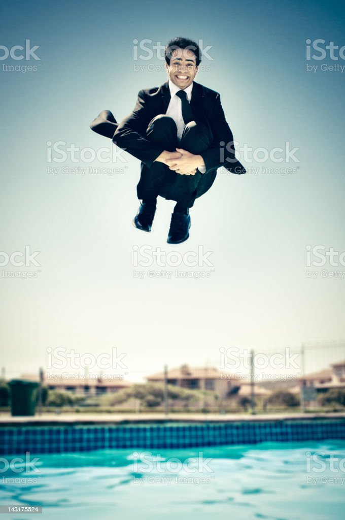 Businessman jumping in the pool stock photo