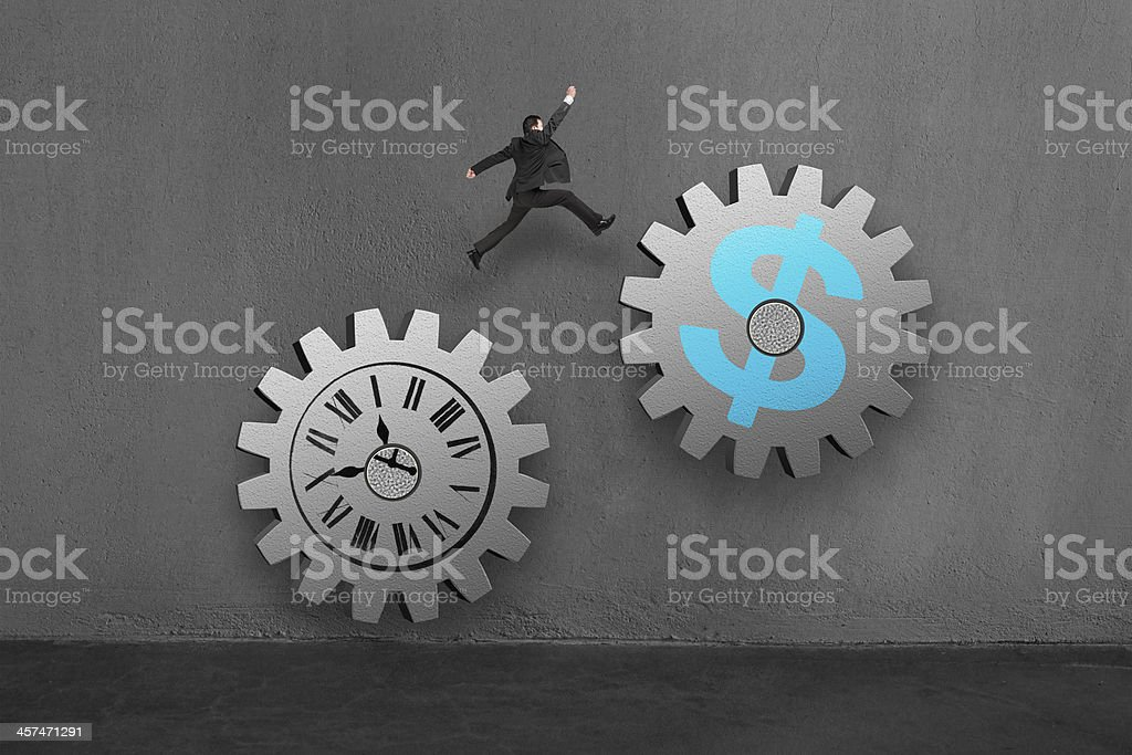 Businessman jumping on 2 large concret gear stock photo