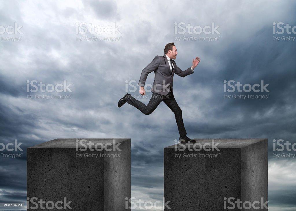 Businessman jumping on concrete blocks stock photo