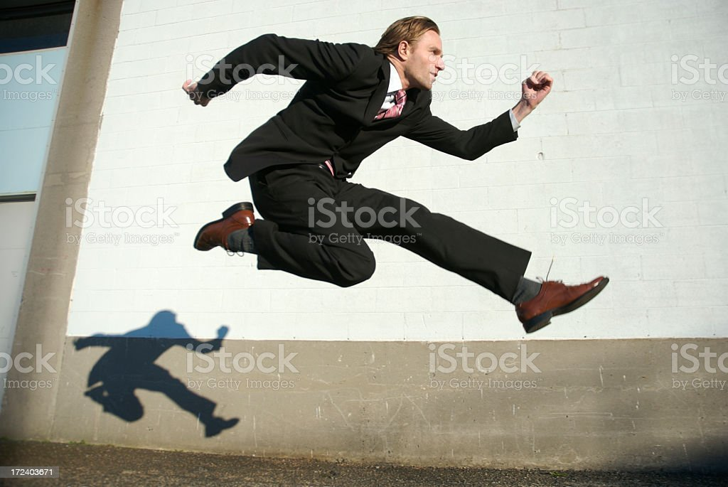 Businessman Jumping Outdoors Against White Wall royalty-free stock photo