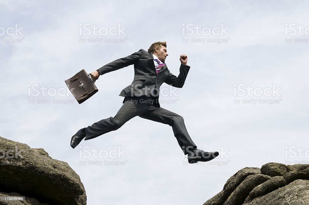 Businessman Jumping Outdoors Between Rock and Hard Place White Sky stock photo