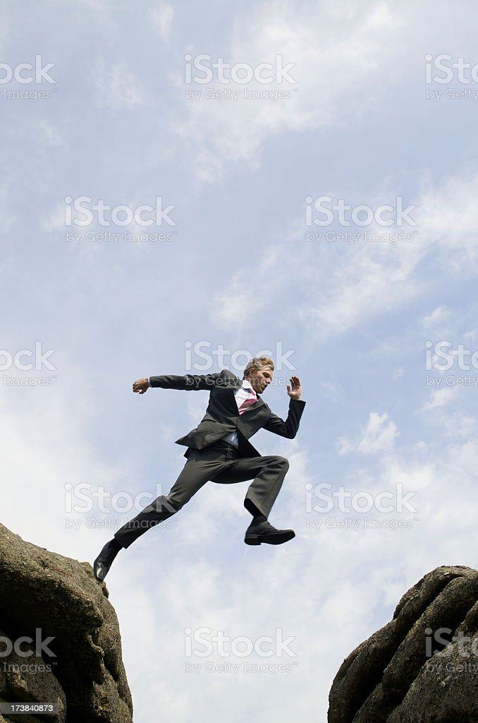 Businessman Jumping Outdoors Over Valley Between Rocks stock photo