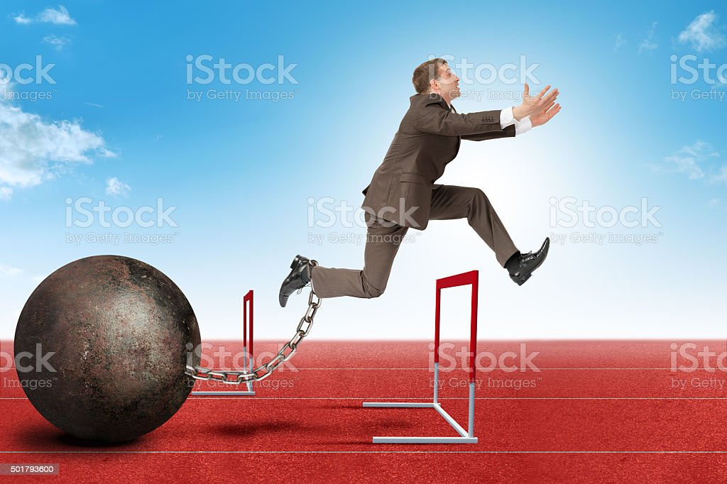 Businessman jumping over barrier stock photo