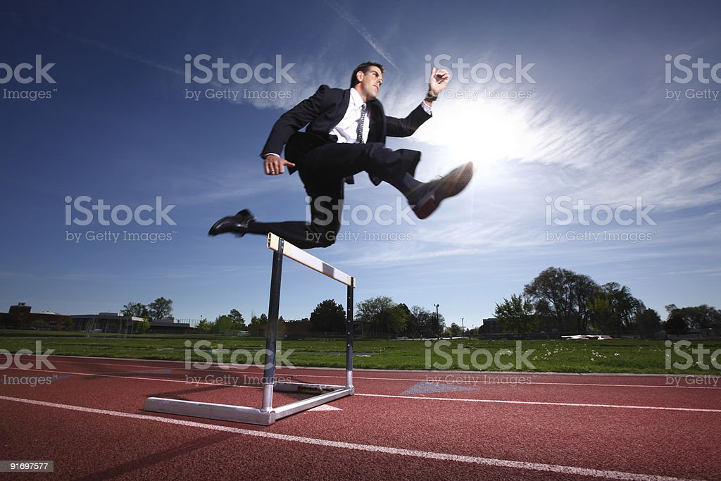 Businessman jumping over hurdle stock photo