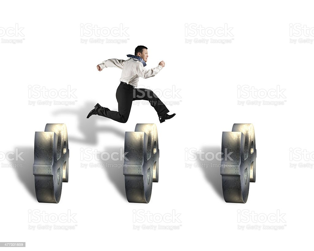 businessman jumping over money symbol obstacles stock photo