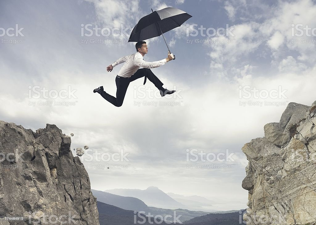 Businessman jumping over the mountains royalty-free stock photo