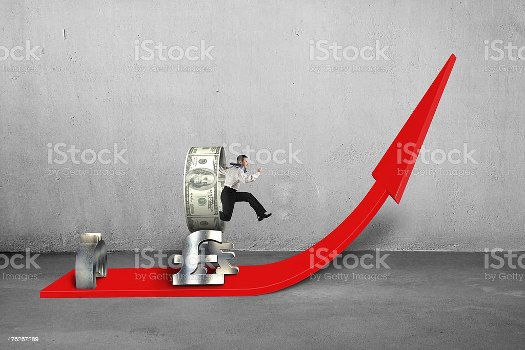 Businessman jumping through money circle stacking on growing red arrow stock photo