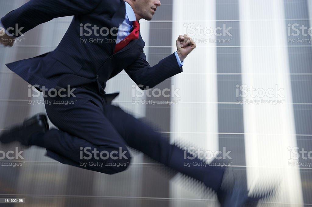 Businessman Jumping with Speed Across Shiny Metal Office Building royalty-free stock photo