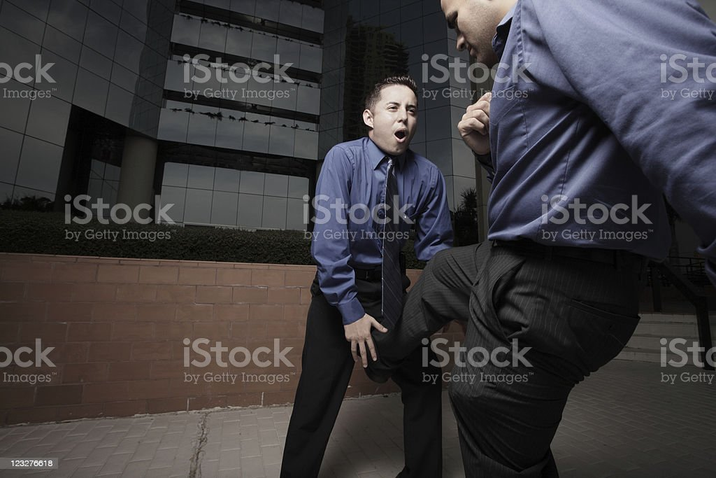 Businessman kicking in the groin stock photo