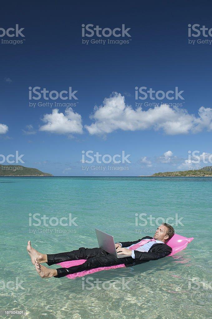 Businessman Kicks Back on Lilo w Laptop royalty-free stock photo