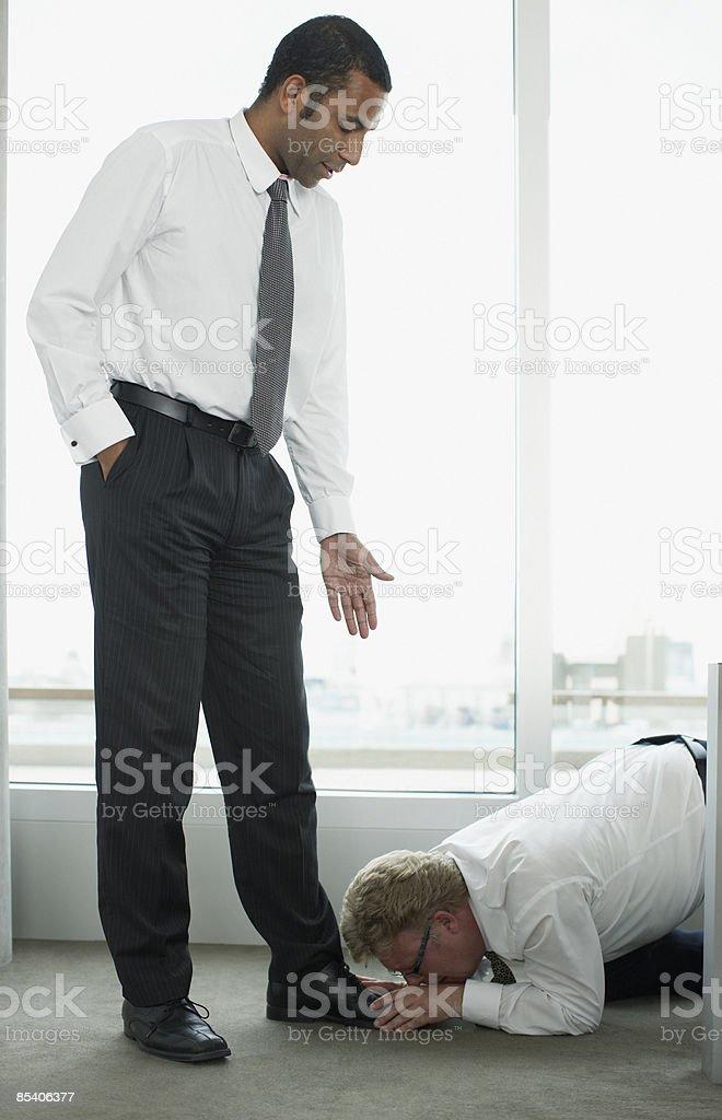 Businessman kissing boss feet stock photo
