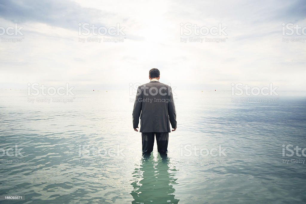 businessman knee-deep in water stock photo