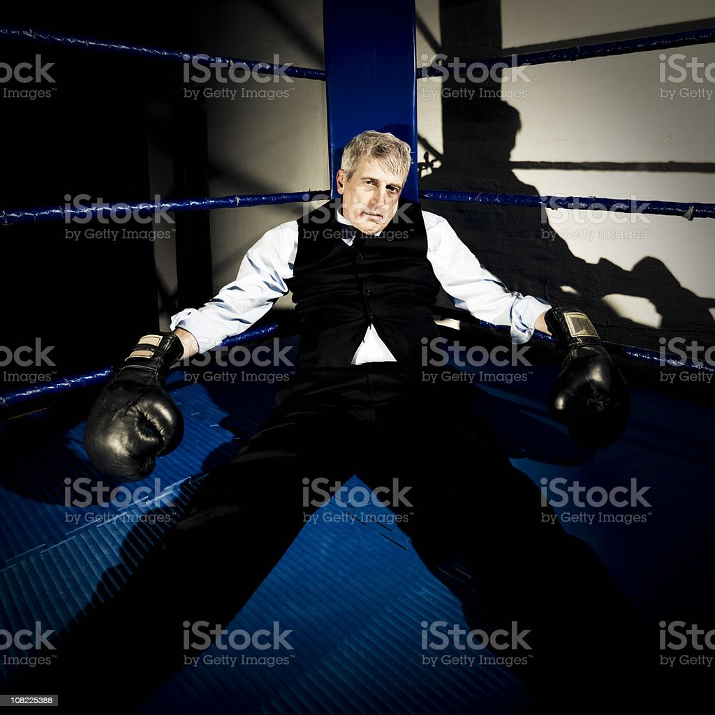 Businessman Knocked out in boxing ring corner royalty-free stock photo