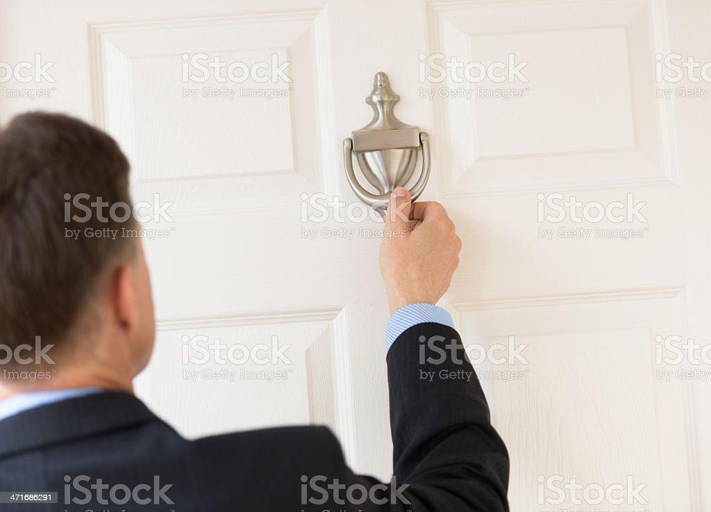 Businessman Knocking Door Knocker stock photo