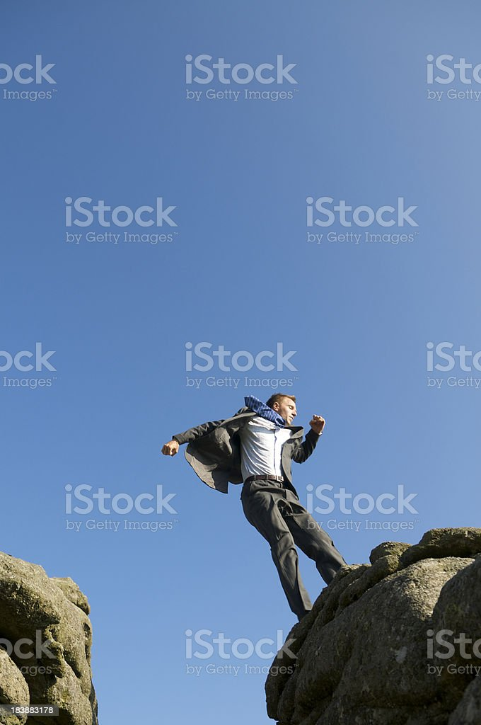 Businessman Lands at the Edge of a Rock Cliff royalty-free stock photo