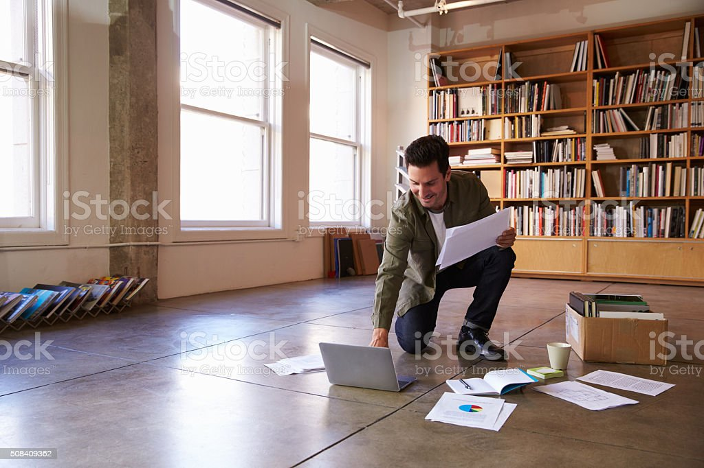Businessman Laying Documents On Floor To Plan Project stock photo