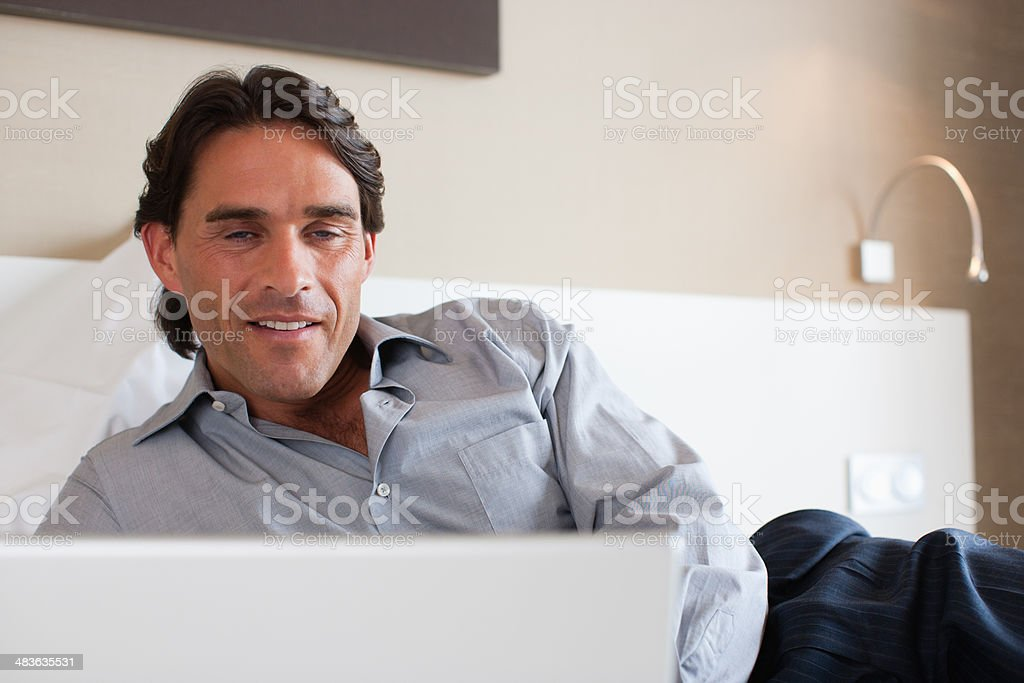 Businessman laying on bed in hotel room stock photo