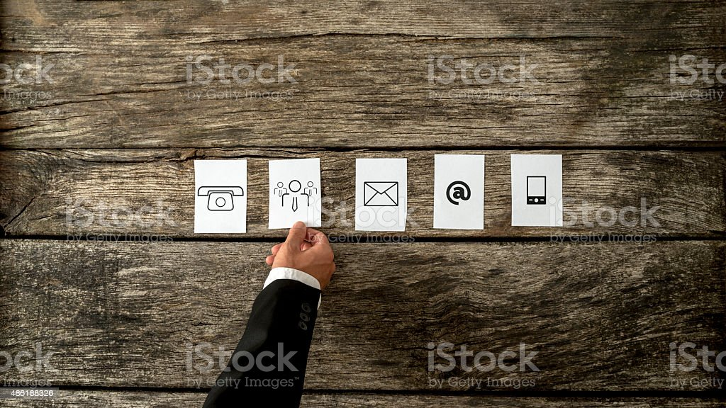 Businessman laying out white cards with communication and people icons stock photo