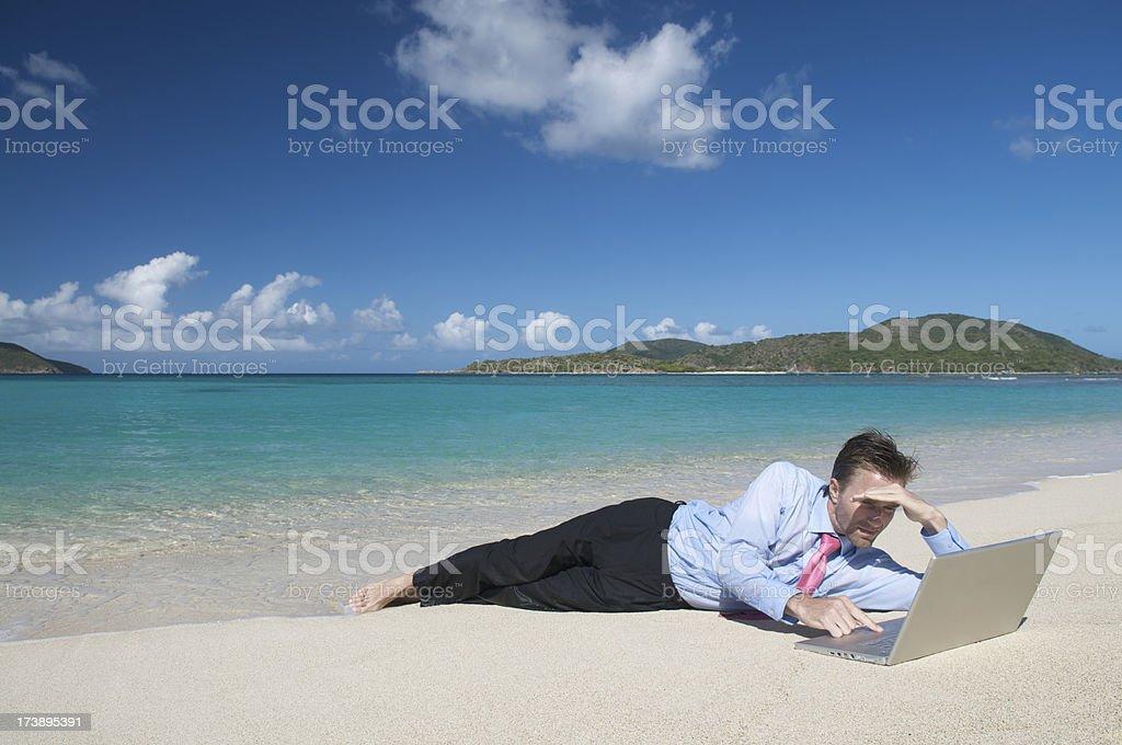 Businessman Lays on Beach w Laptop stock photo